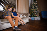 Beautiful young couple in the New Year atmosphere with puppies of the Husky - 183690722