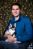 man in a Christmas atmosphere with a Husky puppy - 183691920