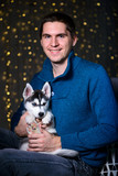 man in a Christmas atmosphere with a Husky puppy - 183691931