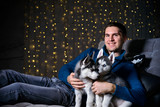 man in a Christmas atmosphere with a Husky puppy - 183691941