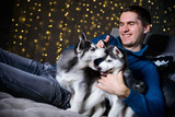 man in a Christmas atmosphere with a Husky puppy - 183691954