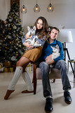 Beautiful young couple in the New Year atmosphere with puppies of the Husky - 183692148