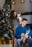 Beautiful young couple in the New Year atmosphere with puppies of the Husky - 183692197