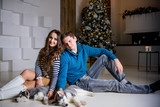 Beautiful young couple in the New Year atmosphere with puppies of the Husky - 183692305