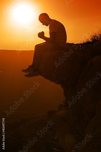 Praying Man Sitting on Rock Poster