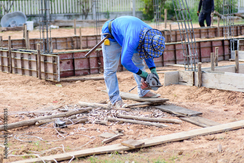 The worker holding wood cutter and cutting wood on the ground at construction site