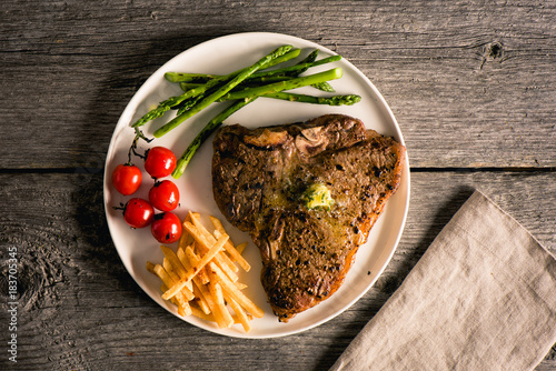 Plexiglas Steakhouse Cooked and plated steak on wood background with fries, tomato, asparagus, sage butter and linen napkin