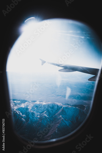 cold blue airplane shot of snowy mountains with lens flair