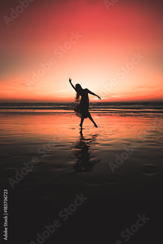 Plexiglas Strand silhouetted girl dancing at sunset on the beach