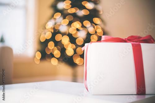 Christmas present with blurred Christmas tree lights