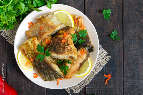 Pieces of roasted carp with lemon and greens on a plate on a dark wooden background. Top view. - 183710364