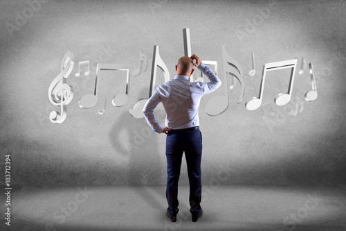 Fotobehang Muziek Businessman in front of a wall with 3d render music notes