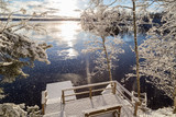 Beautiful view of Lake Pyhäjärvi, snowy trees and pier and snow falling from trees on a sunny day in the winter in Tampere, Finland. - 183716356
