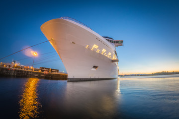 large cruise ship moored at pier at sunset