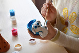 Making toys, paints a pottery clay dog figure with gouache. Indoors creative leisure for children. Supporting creativity, learning by doing, DIY project, hand craft. Master class of art. - 183718357