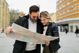 Smiling young attractive couple looking at map - 183723394