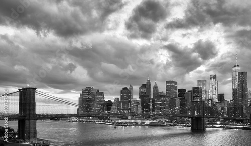 Foto op Aluminium New York Black and white picture of Manhattan and Brooklyn Bridge with dramatic cloudscape at dusk, New York, USA.