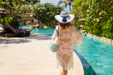 Woman walking near swimming pools in tropical luxury resort - 183728304