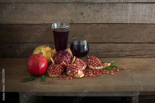 Pomegranate with juice and pile of seeds on the plank in dim light