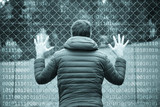 Man standing and holding his hands on fence. Binary numbers background. - 183734717