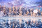 Blue ice and cracks on the surface of the ice. Frozen lake in winter mountains. It is snowing. The hills of pines. Winter. Carpathian Ukraine Europe - 183742534