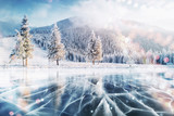 Blue ice and cracks on the surface of the ice. Frozen lake in winter mountains. It is snowing. The hills of pines. Winter. Carpathian Ukraine Europe - 183742540