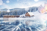 Blue ice and cracks on the surface of the ice. Frozen lake in winter mountains. It is snowing. The hills of pines. Winter. Carpathian Ukraine Europe - 183742564