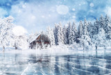 Blue ice and cracks on the surface of the ice. Frozen lake in winter mountains. It is snowing. The hills of pines. Winter. Carpathian Ukraine Europe - 183742570