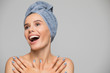 Beautiful spa smiling woman isolated on grey background. She after bath with towel on head.