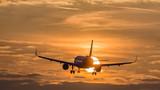 Flugzeug im Landeanflug bei Abendrot