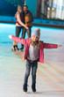 adorable little girl standing with open arms and smiling at camera while parents standing behind on rink