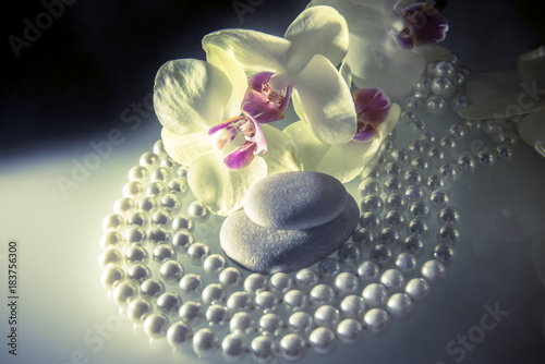 In de dag Spa flat stones on a white glass on the background of yellow orchids