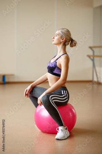 Sticker Slim blonde sporty girl at the gym with a pilates ball.