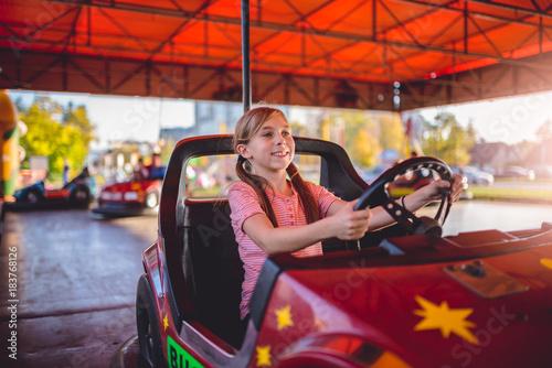 Foto op Aluminium Amusementspark Girl driving electric cars in amusement park