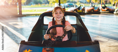 Fotobehang Amusementspark Girl driving electric cars in amusement park
