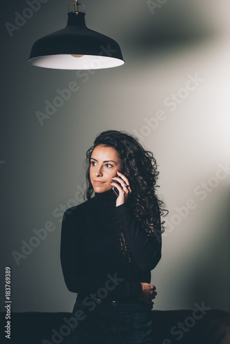 Young woman talking by mobile phone Poster
