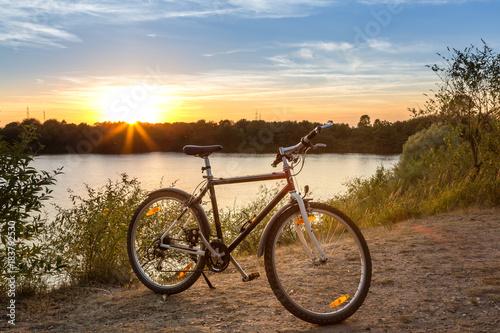 Fahrrad am Ufer eines Sees beim Sonnenuntergang