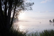 Morning mist over lake with sailboat - 6