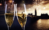 celebrating new year's eve in the city - toasting with champagne glasses in front of Big Ben- holiday lights and fireworks in the background - 183832555