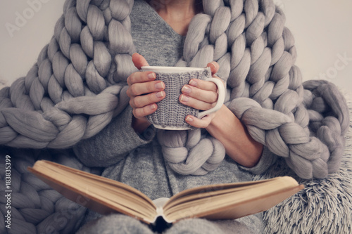 Leinwandbild Motiv Cozy Woman covered with warm soft merino wool blanket reading a book. Relax, comfort lifestyle.