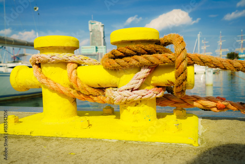 Sailing ropes tied around yellow marina bollard