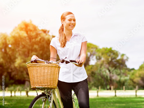 Beautiful young blond woman with bike in park