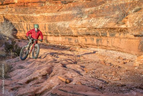 riding fat bike on slickrock at canyon bottom