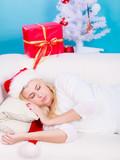 girl wearing santa hat sleeping on sofa at home - 183870924