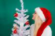 Woman in Santa hat decorating Christmas tree
