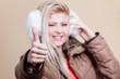 Woman wearing winter furry earmuffs having fun