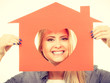 Smiling girl holding red paper house with heart shape