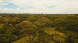 Amazingly shaped Chocolate hills on sunny day on Bohol island, Philippines. Aerial view Chocolate Hills in Bohol, Philippines are earth mounds scattered all over the town of Carmen. 4K video. Travel - 183876354