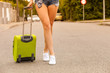 Attractive woman legs walking with green suitcase