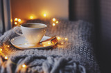 cozy winter or autumn morning at home. Hot coffee with gold metallic spoon, warm blanket, garland and candle lights, swedish hygge concept. - 183905726